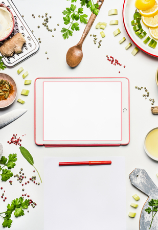 Healthy eating ingredients around tablet with copy space and blank paper with point pen on white desk background , top view, frame. Modern cooking , clean diet nutrition or detox food concept