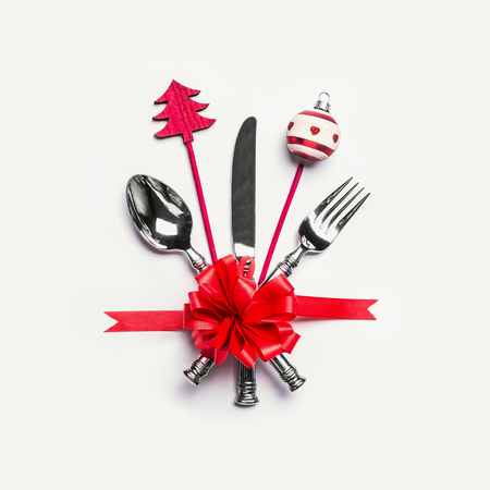 Christmas table place setting with cutlery, red ribbon and minimal decoration on white desk background, top view. Layout for holiday greeting card, festive dinner invitation