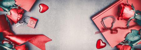 愛とバレンタインデーのコンセプト。素敵な赤いバラ、デートアクセサリー、ハート、本、ロックと灰色の机の背景、バナー、トップビューのキー
