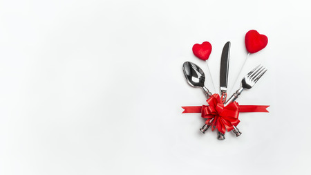 Festive table with red bow, cutlery and two hearts on white background, banner. Layout for Valentines day dinner invitation or menu, banquet, celebration, event