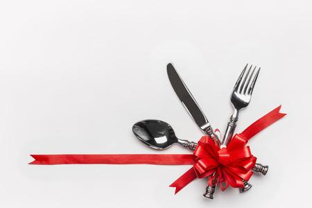 お祝いテーブルの場所の設定カトラリーと赤いリボン白い背景の上のリボンとバナーします。クリスマス ディナーの招待状や記念日、宴会、お祝い 写真素材