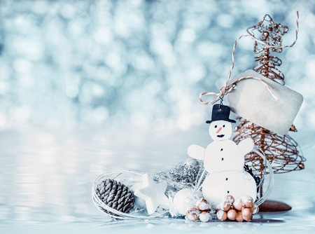 Card with snowman, tag mock up and Christmas tree on blue bokeh background, front view