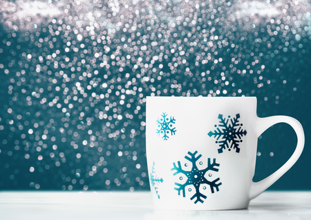 White mug with snowflakes on table at blue background with bokeh, front view concept. Winter holidays layout