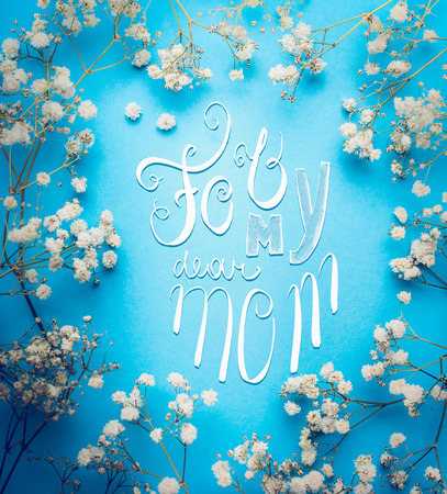 Mothers day greeting card with For my dear mom lettering and lovely little white Gypsophila flowers on blue background, square