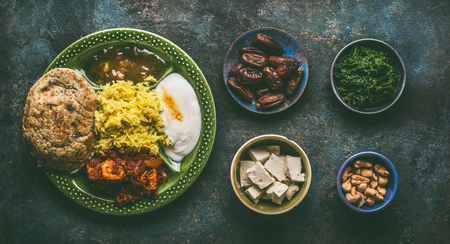 Various Indian foods in bowls on dark rustic background, top view