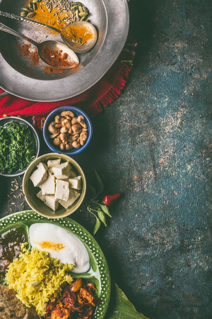 Indian cuisine meals in bowls with spices on dark rustic background, top view, copy space Stock Photo