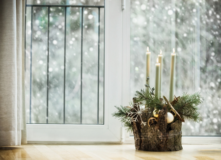 Winter cozy home decoration and festive holiday atmosphere with burning  candles, fir branches and snowflakes in living room at window with snowfall. Decorated Advent wreath