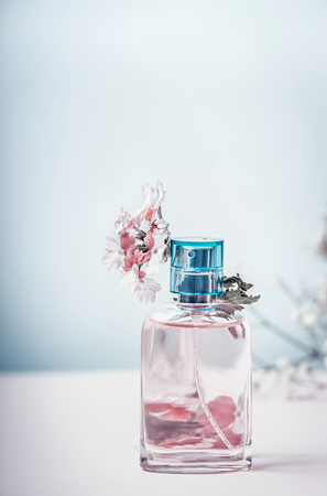 Perfume bottle with flowers, front view. Perfumery, cosmetics, botanical fragrance concept. Pastel color. Beauty concept