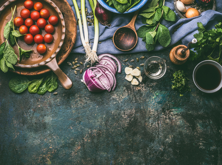 Vegetarian cooking ingredients with fresh seasoning on rustic kitchen table with spoon , top view, place for text.  Clean, vegan food and healthy eating.