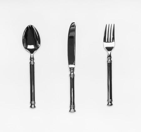 白い背景にフォーク、ナイフ、スプーンを備えたテーブルシルバーウェアカトラリー設定、トップビュー