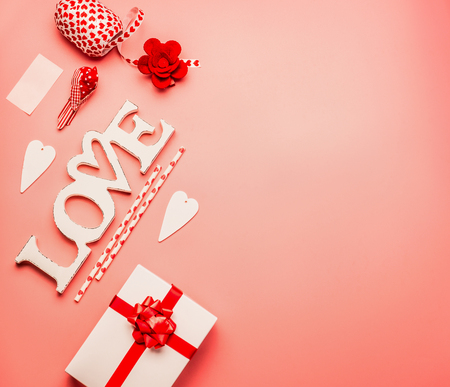 Valentines day background with flat lay of word Love, hearts, gift box with red ribbon and greeting decoration, top view, copy space