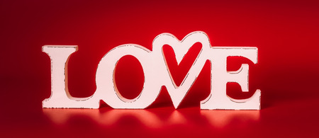 Word Love on red background, front view. Valentines day concept