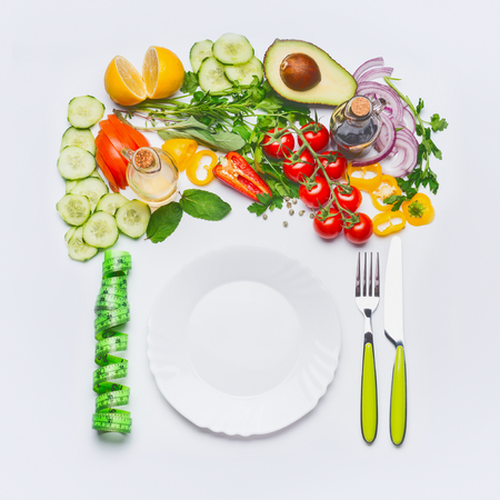 Healthy clean eating or diet food concept. Various salad vegetables with white plate , cutlery and green measuring tape on white background, top view, flat lay, frame.