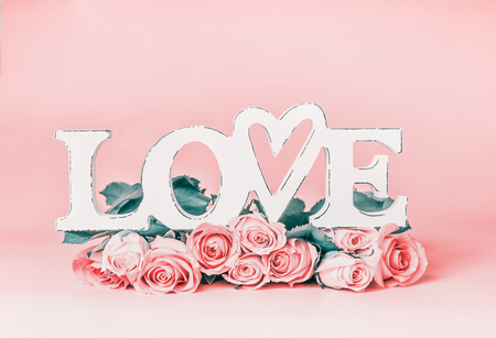 Word LOVE on pastel pink background with roses bunch, front view. Creative female holidays layout with copy space for greeting