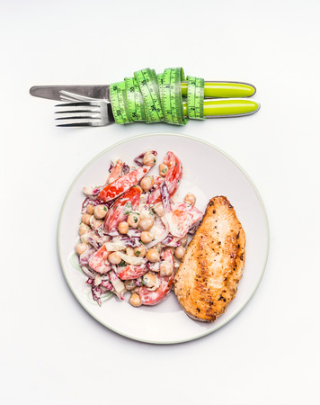 Healthy dieting meal . Chickpeas salad and grilled chicken breast with cutlery and measuring tape on white background, top view