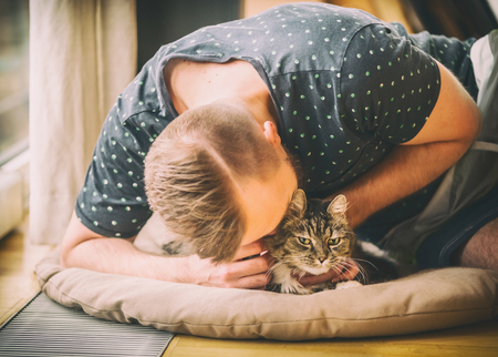 Young man cuddling with his cat on wooden floor, cozy home scene