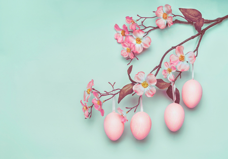 Pastel pink Easter eggs hanging on spring blossom branch at blue turquoise background, copy space for greeting or invitation