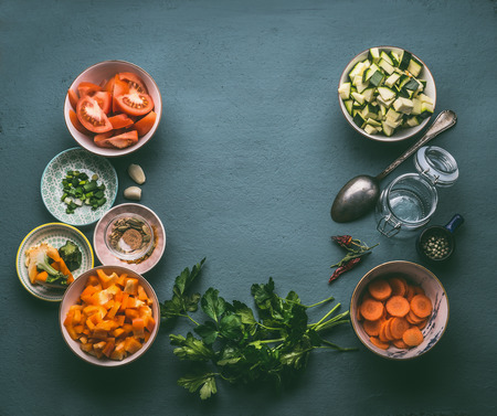 Food background with fresh diced vegetables , cooking spoon and glass jar, top view, frame. Healthy vegetarian food and cooking concept. Homemade lunch in jar making ingredients.