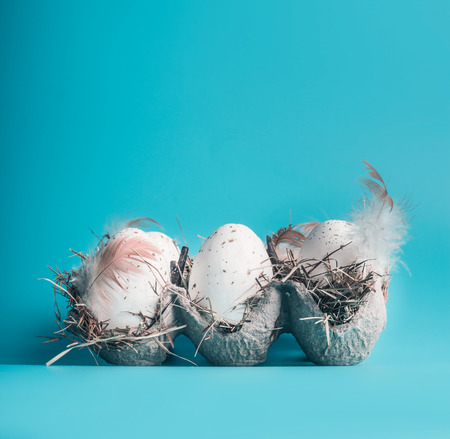 Eggs in carton box on blue background, front view. Easter layout concept
