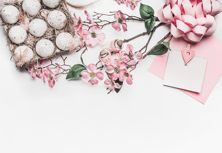 Pastel pink Easter greeting card mock up with blossom decoration, feathers, eggs in carton box on white desk background, top view, flat lay, border, close up Stok Fotoğraf
