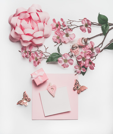 Pretty pastel pink greeting card mock up with blossom decoration, hearts, little gift box and bow on white desk background, top view, flat lay. Wedding invitation  layout or Mother Day  concept