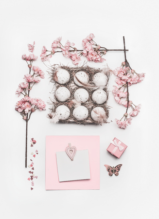 Beautiful pastel pink Easter layout with blossom decoration, hearts, eggs in carton box and greeting card mock up on white desk background, top view, flat lay. Standard-Bild - 95928997