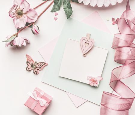 花の装飾、リボン、ハートとカードモックアップ白い机の背景、トップビュー、フラットレイと美しいパステルピンクのレイアウト。結婚式の招待 写真素材