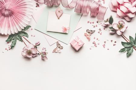 花の装飾、リボン、ハート、弓とカードモックアップ白い机の背景、トップビュー、フラットレイ、ボーダーと美しいパステルピンクのレイアウト