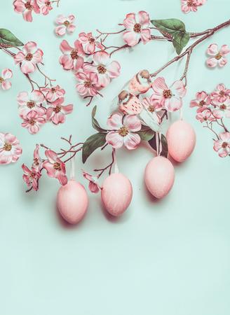 ターコイズの背景にハングエッグと装飾花を持つイースターパステルピンクのレイアウト