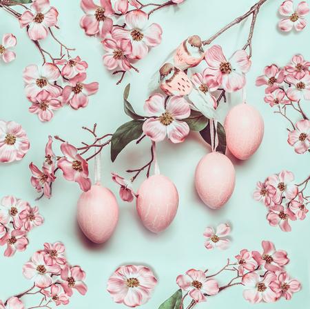 ターコイズの背景にハングエッグと装飾花を持つイースターパステルピンクのパターン 写真素材