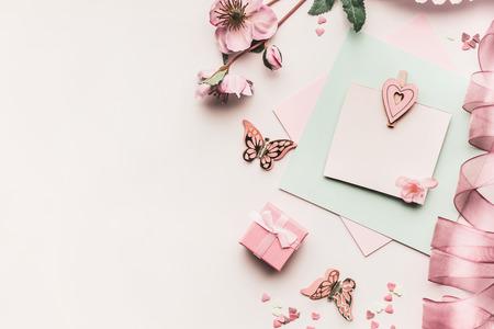 Mock up de tarjeta de felicitación de vacaciones femeninas en color pastel pálido con flores, caja de regalo, cinta y corazón sobre fondo blanco de escritorio, vista superior. Estilo plano laico.