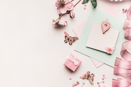Mock up of feminine holidays greeting card in pale pastel color with flowers, gift box,ribbon and heart on white desktop background, top view. Styled flat lay .