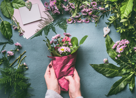Female hand making beautiful bouquet of pink flowers on florist workspace, top view. Woman wrap bouquet in wrapping paper, step by step