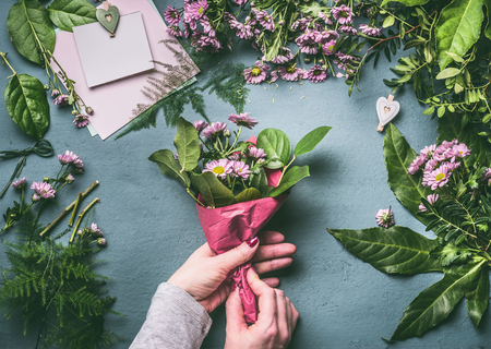 Female hands making lovely bouquet of pink flowers with wrapping female hands making lovely bouquet of pink flowers with wrapping paper on florist workspace top mightylinksfo