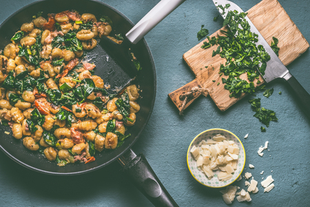 Vegetarian meal with Potato gnocchi , spinach and vegetables  sauce in frying pan on rustic table , top view
