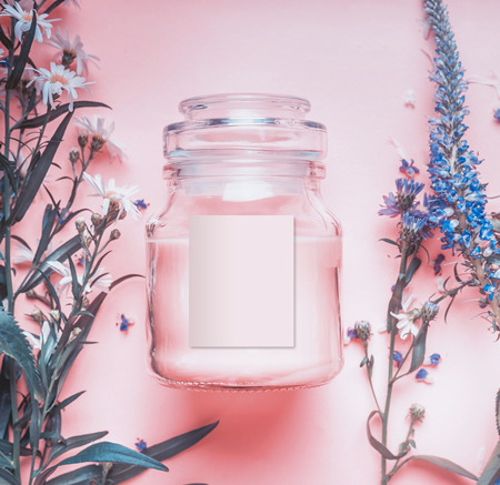 Natural cosmetics jar with pastel pink cream or peeling , herbal leaves and wild flowers, blank label for branding mock-up on pastel background, top view Stock Photo