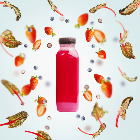 Pink smoothie bottle with flying berries and leaves on light blue background. Healthy detox beverages, dieting, clean eating, vegetarian, vegan, fitness or healthy lifestyle concept