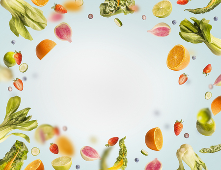 Various flying or falling summer fruits, berries and vegetables on light blue background, frame. Healthy detox food layout concept