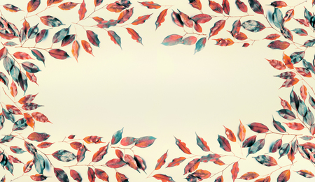 Beautiful frame made of autumn colored branches and leaves on pastel  background. Flat lay, top view, horizontal Standard-Bild - 97608405