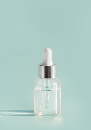 Cosmetic transparent liquid in glass bottle with dropper. Serum skin care product on light mint background, front view with copy space. Beauty product concept. Blank label for branding mock-up
