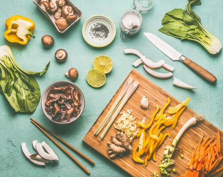 Asian food flat lay with chopsticks and tasty ingredients: Mu Err Mushrooms , various vegetables , pok choi , coconut milk and lemongrass  , top view, copy space. Vegetarian or vegan asian cuisine