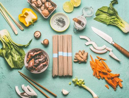 Asian food flat lay with tasty ingredients: Mu Err Mushrooms , various vegetables , pok choi , coconut milk, lemongrass and noodles , top view, copy space. Vegetarian or vegan asian cuisine Stock Photo