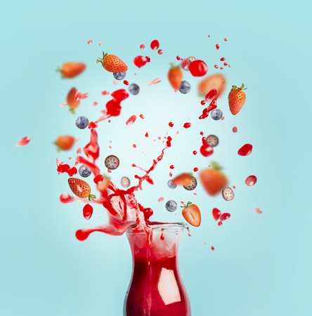Red juice or smoothie drink is poured out of glass bottle with splash and berries ingredients on turquoise background, front view. Healthy summer beverage concept