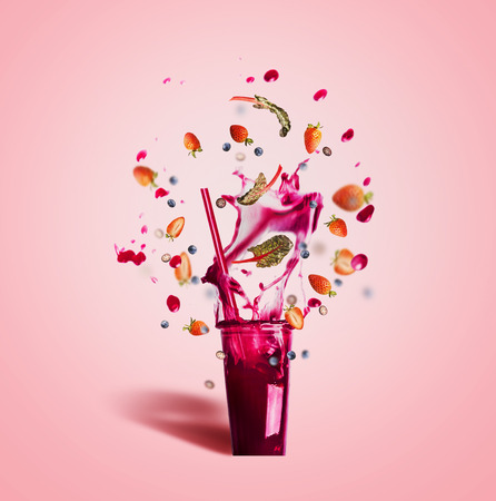 Glass with drinking  straw and purple splash summer beverage: smoothie or juice with flying berries ingredients on pink background, front view