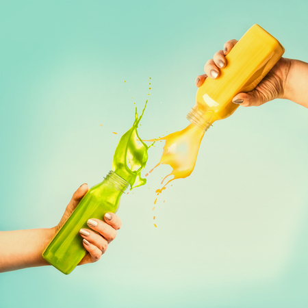 Female hands holding bottles with yellow and green splash smoothie or juice on blue background with tropical leaves and fruits. Summer beverages concept. Banque d'images