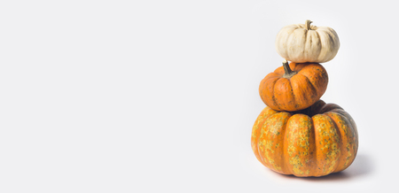 Stack of ripe pumpkins on white background, front view, copy space for text Stock Photo