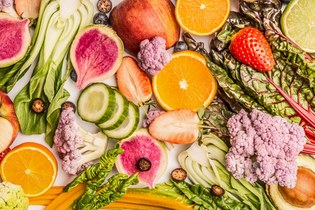 Colorful fruits and vegetables background with half of oranges, and berries , top view. Healthy food and clean eating ingredients concept Stock Photo