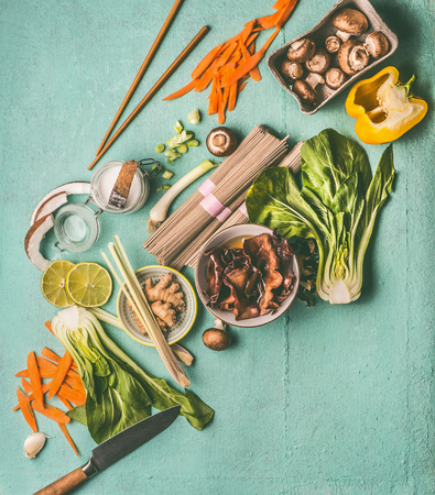 Asian food ingredients for tasty vegetarian cooking and eating: noodles, pak choy, chopped vegetables, chopsticks, Mu Err mushrooms, lemon grass, coconut, lime and spices, top view