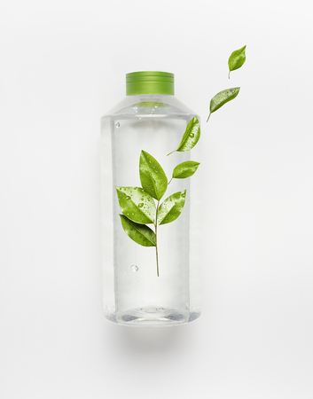 Transparent liquid bottle with green lid. Clear nature water with green flying leaves and branding mock up on white desk background , top view.
