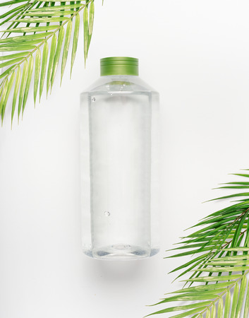 Transparent liquid bottle with green lid on white desk background with tropical palm leaves, top view